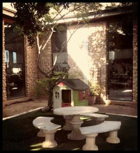 Espacio con asientos y mesa con sombra en Única Garden