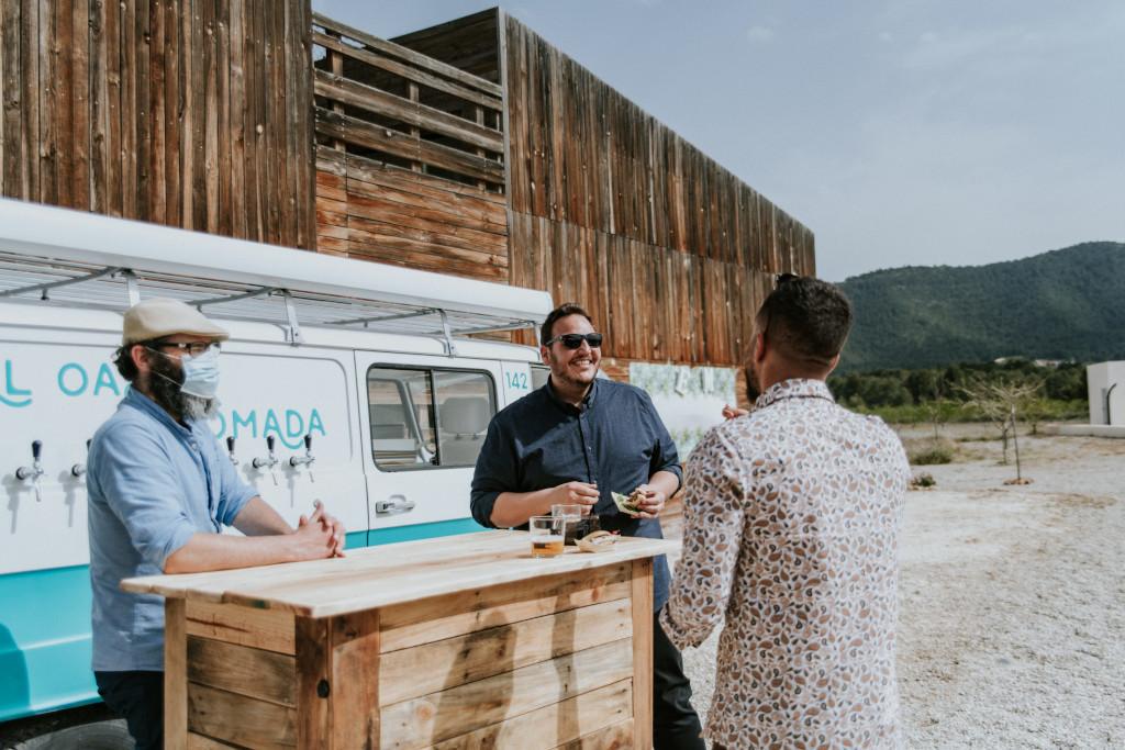 Varias personas disfrutando unas cervezas en el exterior de una casa rural con la tap truck de El Oasis Nomada y una barra de bar de madera