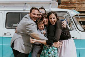 Algunos asistentes a la boda se abrazan delante de nuestra furgoneta Merche