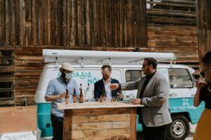 Tres hombres tras la barra de El Oasis Nómada durante una cata guiada de cervezas